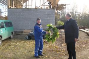 Pagėgių savivaldybės meras Virginijus  Komskis perduoda statybininkams stogo pabaigtuvių vainiką+.